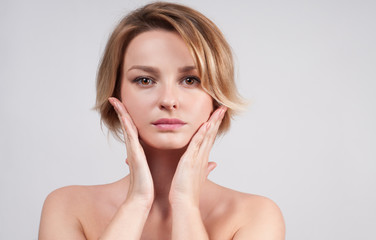 Beautiful woman with clean perfect skin touch own face.