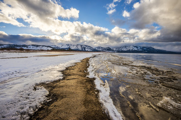 A view looking down Commons Beach in the winter with a dramatic sunset overhead in South Lake Tahoe, California.