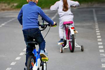 The kids compete on bicycles.