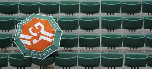 Tennis - French Open - Roland Garros - A spectator holds an umbrella as rain falls at French Open