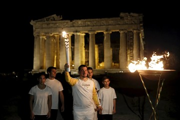 Three times gold Olympic weightlifting medalist Dimas lights a cauldron with the Olympic Flame, as his children stand by, atop the Acropolis hill as the Parthenon temple is seen in the background in Athens