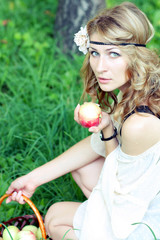 nice young girl with fresh red apple in the summer park