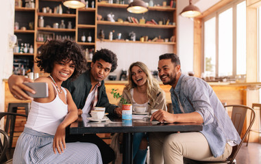 Diverse group of friends taking selfie on smart phone at cafe