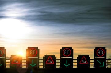 Fototapete - Verkehrsleitsystem Tempo 80 Schilderbrücke Baustellenwarnung im Gegenlicht