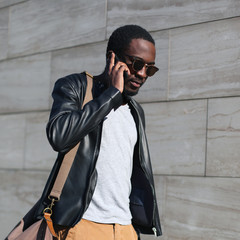 Fashion portrait young confident african man walking and talking on the smartphone in a evening city