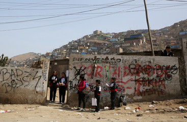 Students wait for a bus at Pamplona Alta shanty town in the San Juan de Miraflores district of Lima