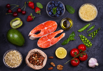 Selection of healthy and good for heart food. Healthy food concept with salmon, fresh vegetables, fruits and ingredients for cooking on dark background. Top view with copy space