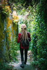 A young woman with blond dreadlocks, back view, goes through the greens. Adventure.