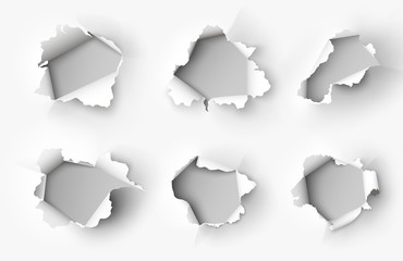 Holes torn in paper on white