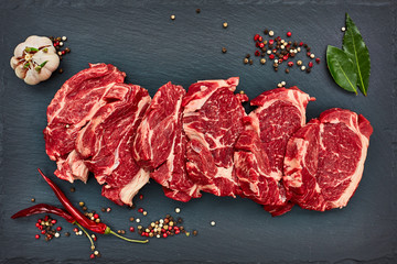Fresh raw beef steaks with chilly pepper on black slate board. Copy space, top view.
