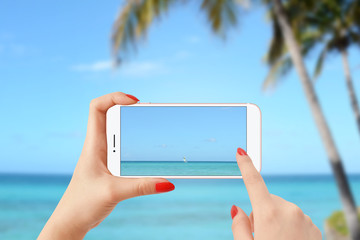 Girl on the beach taking picture of sailing boat on the sea with smartphone