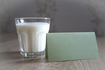 Ein Glas Milch mit Notitzzettel im vordergrund mit dekorativen Hintergrund