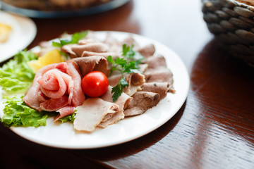 Beautiful patterns, slicing the ham on the plate, snack food. Food plate with delicious salami, pieces of sliced ham, sausage, tomatoes, salad and vegetable - Meat platter with selection