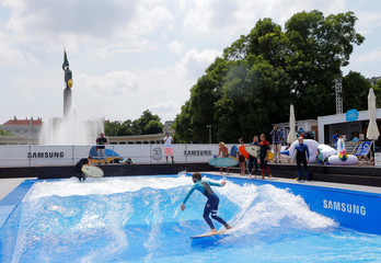 A surfer rides on an artificial wave during the opening of a surfing pool in central Vienna