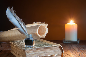 Quill pen and a rolled papyrus sheet on an old book by candle light