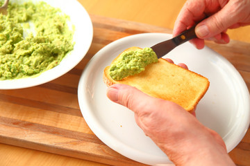 Spreading avocado on toast