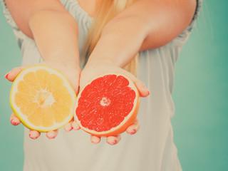 Halfs of yellow red grapefruit citrus fruit in human hands