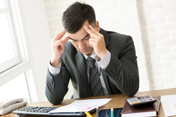 Serious businessman looking at financial document at working table