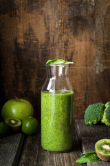 Detox green smoothie in bottle with drinking straw on rustic wooden table. Dieting, healthy eating healthy lifestyle concept