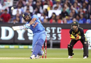 India's Rohit Sharma hits a six while batting with Australia's Matthew Wade watching during their T20 cricket match at the Melbourne Cricket Ground