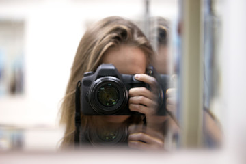 A girl with a camera in a mirror image