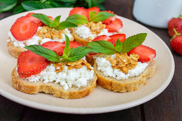 Mini sandwiches with cottage cheese, fresh strawberries, decorated with mint leaves on rye bread  on a dark wooden background. Proper nutrition. Healthy food. Dietary menu