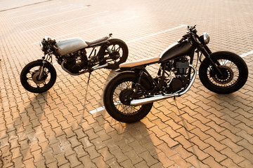 Two cool vintage custom motorcycle caferacer looking in opposite directions on empty rooftop parking lot with backlight sun during sunset. Urban style, hipster lifestyle.