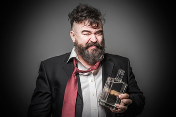 Adult bearded man in suit with a look of disgust on his face holding a bottle of alcohol. Toned
