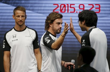 McLaren Formula One drivers Alonso of Spain gives a high five to a fan next to his team mate Button of Britain during a fan meeting at the Honda Motor Co's headquarters in Tokyo