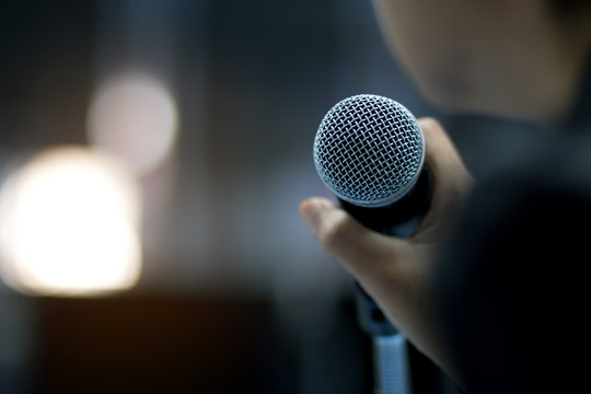 Blurred of businessman or speaker hand holding microphone for speech presentation in conference hall or meeting hall in university