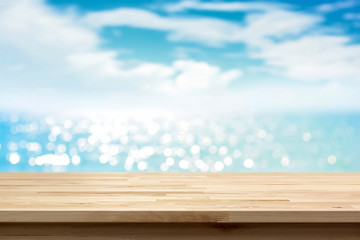 Wood table top on blur shiny sea water and summer sky background