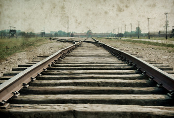 Main gate and railroad to nazi concentration camp of Auschwitz Birkenau. Effect with grunge background, fake old photo