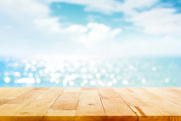 Wood table top on blur sparkling sea water and summer sky background Wall mural