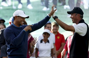 U.S. golfer Woods high fives with compatriot Kuchar during a golf clinic in Mexico City
