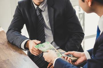 Businessman giving money, Australian dollar bills, to his partner