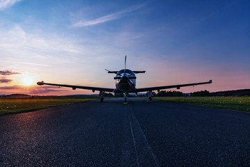 Single turboprop aircraft on evening runway.