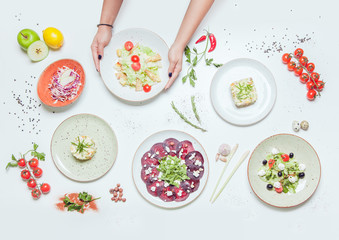 Salads and appetizers on a white table decorated with fruits and herbs.