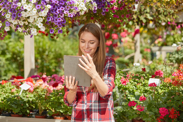 Smiling young female botanist using tablet standing near flowers in the garden in sunny day.