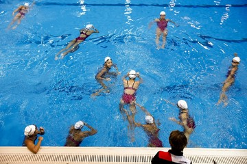 Masayo Imura, the coach of Japan's synchronised swimming team, gives instructions to her swimmers during training session at pool in Tokyo