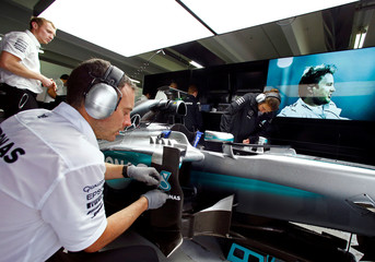 Mechanics work on a Mercedes Formula One car during the Mercedes Benz media day at the Hockenheim racing circuit