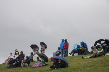 Formula One race fans sit under rain clouds as they watch the qualifying for the U.S. F1 Grand Prix at the Circuit of The Americas in Austin, Texas
