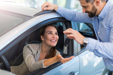 Woman receiving keys from a car dealer
