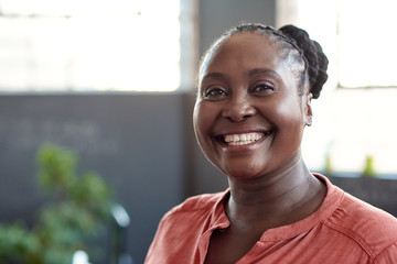 Young African businesswoman smiling confidently in an office Fotoväggar