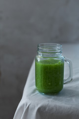 Fresh organic green smoothie with spinach, cucumber on a white tablecloth