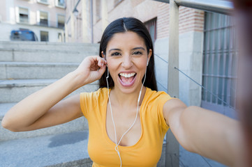 attractive latin woman listening to music on her smart phone
