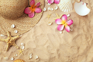 summer hat and seashells on sand, summer background