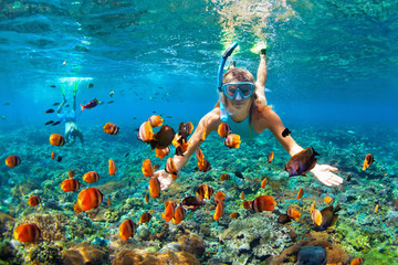 Happy family - couple in snorkeling masks dive deep underwater with tropical fishes in coral reef sea pool. Travel lifestyle, outdoor water sport adventure, swimming lessons on summer beach holiday Wall mural