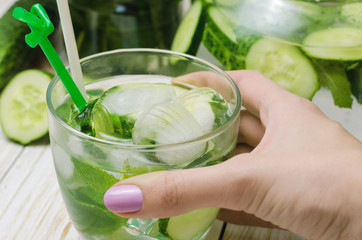 Water with cucumber, mint and ice in glassware in wooden tray, closeup.