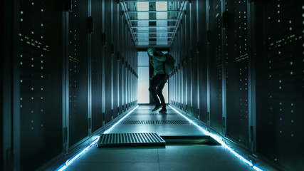 Shot of a Masked Hacker in a Hoodie Walking Away and Watching Back with Laptop in a Corporate Data Center.