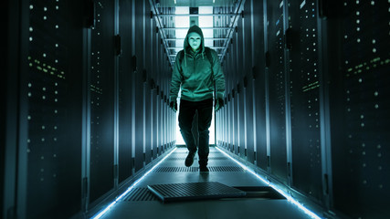 Hooded Hacker in a Mask Walks Through Working Data Center with Open Floor Hatch in the Middle of it.